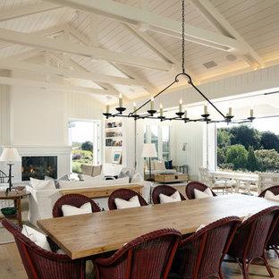 Неиссякаемый источник вдохновения для домашнего уюта: огромная гостиная-столовая в стиле кантри с белыми стенами, паркетным полом среднего тона, стандартным камином и фасадом камина из кирпича