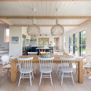 Foto di una sala da pranzo aperta verso il soggiorno costiera con pareti bianche, parquet chiaro, pavimento beige, travi a vista e soffitto in perlinato