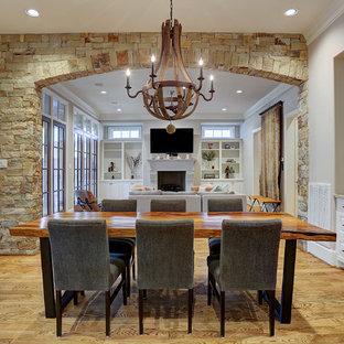 Modelo de comedor tradicional, abierto, con paredes beige, suelo de madera clara, chimenea tradicional, marco de chimenea de hormigón y suelo marrón