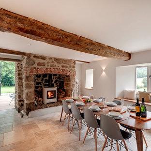 На фото: столовая в стиле кантри с белыми стенами, печью-буржуйкой и фасадом камина из камня с