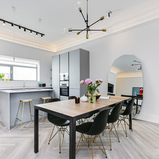 This is an example of a scandi kitchen/dining room in London with grey walls, light hardwood flooring and grey floors.