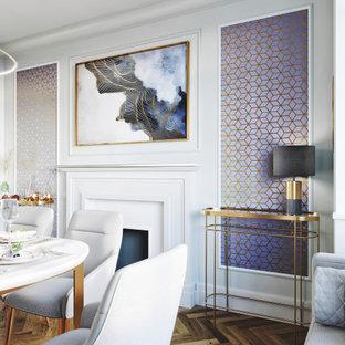 サリーの中くらいのモダンスタイルのおしゃれなダイニング (グレーの壁、ラミネートの床、標準型暖炉、塗装板張りの暖炉まわり、茶色い床、パネル壁) の写真