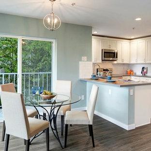 Idee per una sala da pranzo aperta verso la cucina minimal di medie dimensioni con pareti verdi, pavimento in laminato e pavimento marrone