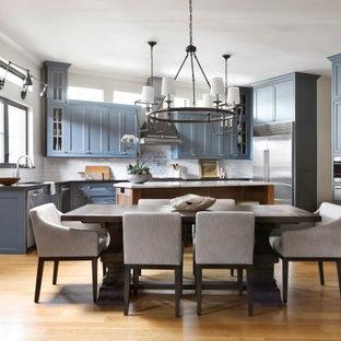 Idée de décoration pour une salle à manger ouverte sur la cuisine tradition avec un sol en bois clair, un mur beige, une cheminée standard, un manteau de cheminée en lambris de bois et un sol marron.