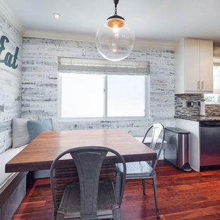 Foto de comedor de cocina ecléctico, pequeño, con paredes grises, suelo laminado, chimenea de esquina, marco de chimenea de baldosas y/o azulejos y suelo marrón