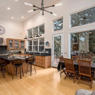 Idee per una grande sala da pranzo aperta verso la cucina minimalista con pareti bianche, parquet chiaro, camino sospeso, cornice del camino piastrellata e pavimento marrone