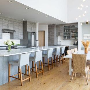 Immagine di una sala da pranzo aperta verso il soggiorno design con pareti grigie, parquet chiaro e pavimento giallo