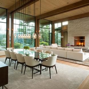 На фото: огромная гостиная-столовая в современном стиле с светлым паркетным полом, стандартным камином, фасадом камина из камня и бежевым полом с