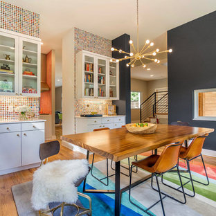 This is an example of an eclectic dining room in Dallas with multi-coloured walls, medium hardwood flooring and brown floors.