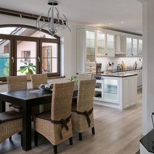 Idée de décoration pour une salle à manger ouverte sur la cuisine tradition de taille moyenne avec un mur blanc, un sol en contreplaqué, une cheminée standard et un sol beige.