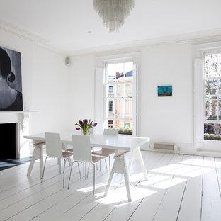 Foto di una sala da pranzo nordica con pareti bianche, pavimento in legno verniciato, camino classico e pavimento bianco