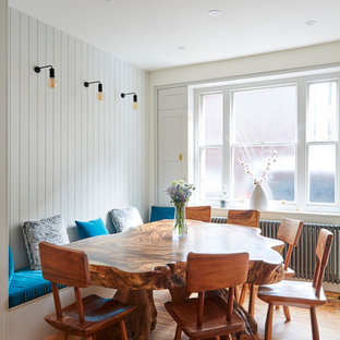 This is an example of a medium sized coastal open plan dining room in London with white walls, light hardwood flooring and brown floors.