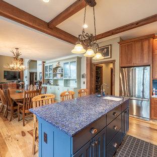 Ejemplo de comedor de cocina rústico, de tamaño medio, con paredes blancas, suelo de madera en tonos medios, chimenea tradicional, marco de chimenea de piedra y suelo amarillo