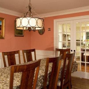 Esempio di una grande sala da pranzo chic chiusa con pareti arancioni, parquet scuro, nessun camino e pavimento marrone
