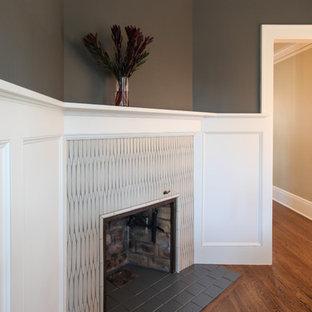 ミネアポリスの中サイズのトラディショナルスタイルのおしゃれな独立型ダイニング (グレーの壁、無垢フローリング、コーナー設置型暖炉、タイルの暖炉まわり、茶色い床) の写真