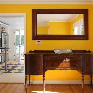 Immagine di una sala da pranzo boho chic con pareti gialle e pavimento in legno massello medio