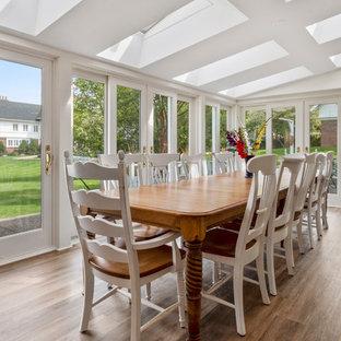 Immagine di una grande sala da pranzo aperta verso il soggiorno stile marino con pareti bianche, pavimento in vinile e pavimento marrone