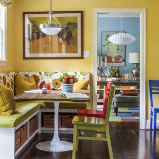Foto de comedor de cocina bohemio, de tamaño medio, sin chimenea, con paredes amarillas y suelo de madera oscura