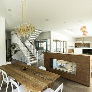 Immagine di una sala da pranzo aperta verso il soggiorno minimal di medie dimensioni con pareti bianche, pavimento in cemento, camino bifacciale, pavimento marrone e cornice del camino in legno