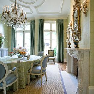 Ispirazione per una grande sala da pranzo classica chiusa con pareti verdi, pavimento in legno massello medio, camino classico e cornice del camino in pietra