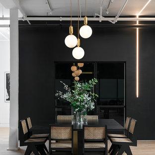 Diseño de comedor urbano, grande, sin chimenea, con paredes negras, suelo de madera clara y suelo beige