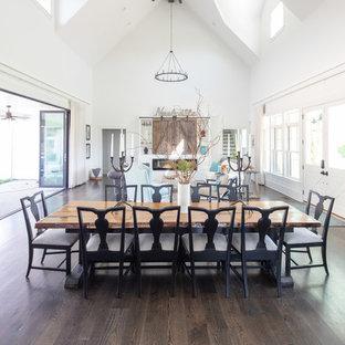 Diseño de comedor campestre, grande, abierto, con paredes blancas, suelo de madera en tonos medios, chimenea tradicional, marco de chimenea de madera y suelo marrón