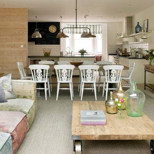 Cette image montre une très grande salle à manger ouverte sur la cuisine style shabby chic avec un mur beige, un sol en bois clair, aucune cheminée et un sol beige.