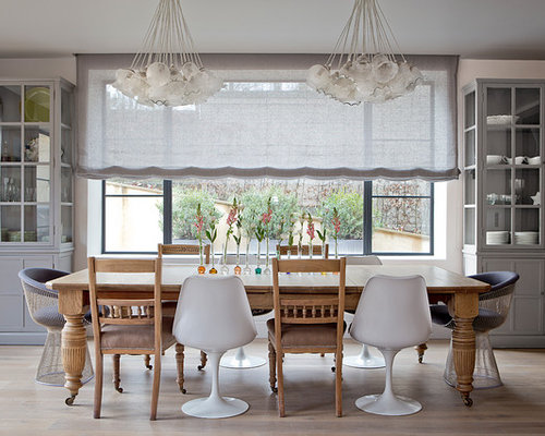 large trendy dining room photo in london with white walls and light