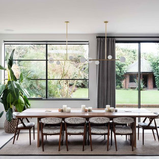 Photo of a large contemporary dining room in London with white walls, concrete flooring and grey floors.
