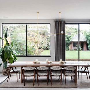 Esempio di una grande sala da pranzo design con pareti bianche, pavimento in cemento e pavimento grigio