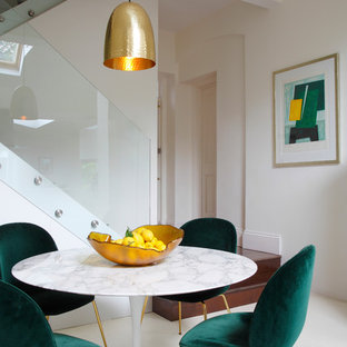 This is an example of a dining room in London with beige walls and beige floors.