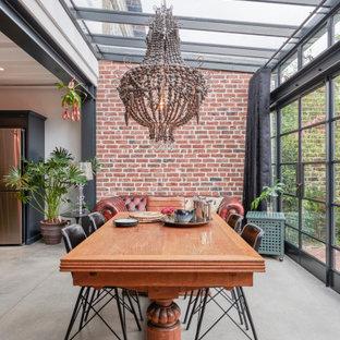 Aménagement d'une salle à manger industrielle avec un plafond voûté et un mur en parement de brique.