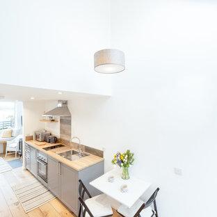 Immagine di una piccola sala da pranzo aperta verso il soggiorno contemporanea con pareti bianche, pavimento in legno massello medio, stufa a legna, cornice del camino in pietra e pavimento marrone