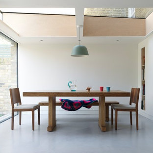 Design ideas for a medium sized modern enclosed dining room in London with white walls, concrete flooring and grey floors.