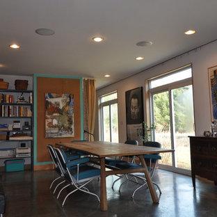 Foto di una sala da pranzo aperta verso la cucina contemporanea di medie dimensioni con pareti arancioni, pavimento in cemento, nessun camino e pavimento grigio