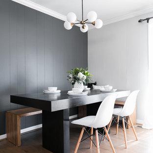 Foto di una sala da pranzo minimal con pareti nere, pavimento in legno massello medio e pavimento marrone
