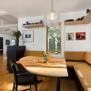 Inspiration pour une salle à manger ouverte sur le salon nordique de taille moyenne avec un mur blanc, un sol en bois brun et un sol orange.