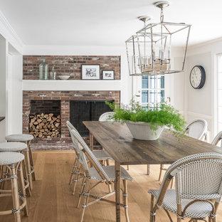 Пример оригинального дизайна: столовая в стиле кантри с белыми стенами, паркетным полом среднего тона, стандартным камином и фасадом камина из кирпича
