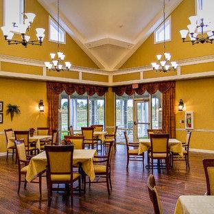 Idee per un'ampia sala da pranzo aperta verso il soggiorno design con pareti gialle, pavimento in vinile e pavimento marrone