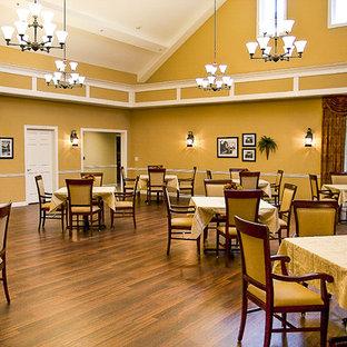 Immagine di un'ampia sala da pranzo aperta verso il soggiorno design con pareti gialle, pavimento in vinile e pavimento marrone