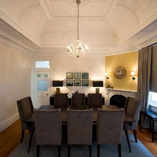 Idee per una sala da pranzo aperta verso il soggiorno classica di medie dimensioni con pareti gialle, pavimento in legno massello medio, camino ad angolo e cornice del camino in intonaco
