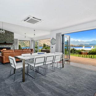 Cette photo montre une grand salle à manger ouverte sur le salon tendance avec un mur blanc, un sol en bois brun, un poêle à bois, un manteau de cheminée en pierre de parement et un sol marron.