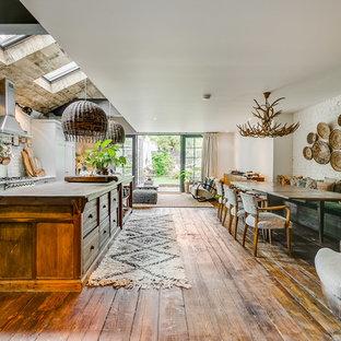 Foto di un'ampia sala da pranzo aperta verso il soggiorno boho chic con pareti bianche, pavimento in legno massello medio e pavimento marrone