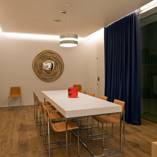 Photo of a medium sized modern dining room in London with white walls, light hardwood flooring and beige floors.