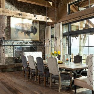 Diseño de comedor rústico, extra grande, abierto, con chimenea de doble cara, marco de chimenea de piedra, suelo marrón y suelo de madera oscura