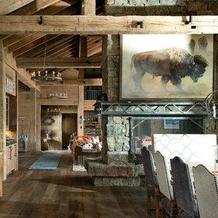 Inspiration för mycket stora rustika kök med matplatser, med bruna väggar, mellanmörkt trägolv, en dubbelsidig öppen spis, en spiselkrans i sten och brunt golv