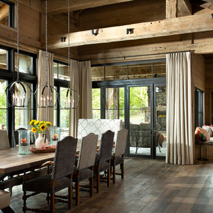 Example of a huge mountain style brown floor and dark wood floor kitchen/dining room combo design in Other with brown walls