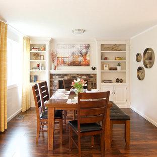 Idee per una sala da pranzo tradizionale chiusa e di medie dimensioni con pareti bianche, pavimento in laminato, camino classico, cornice del camino in mattoni e pavimento marrone