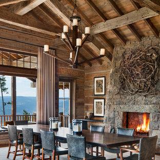 Idee per un'ampia sala da pranzo stile rurale con pareti marroni, pavimento in legno massello medio, camino classico, cornice del camino in pietra e pavimento marrone