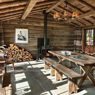 Cette image montre une petit salle à manger chalet avec un mur marron, un poêle à bois, un manteau de cheminée en métal et un sol bleu.